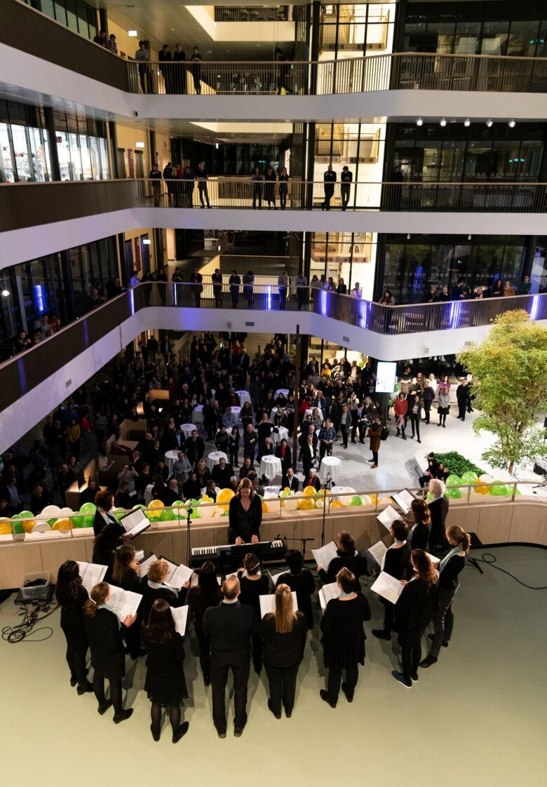 choir performing in the atrium of Biomedicum at the inauguration. Audience is spread out on different levels of the building.