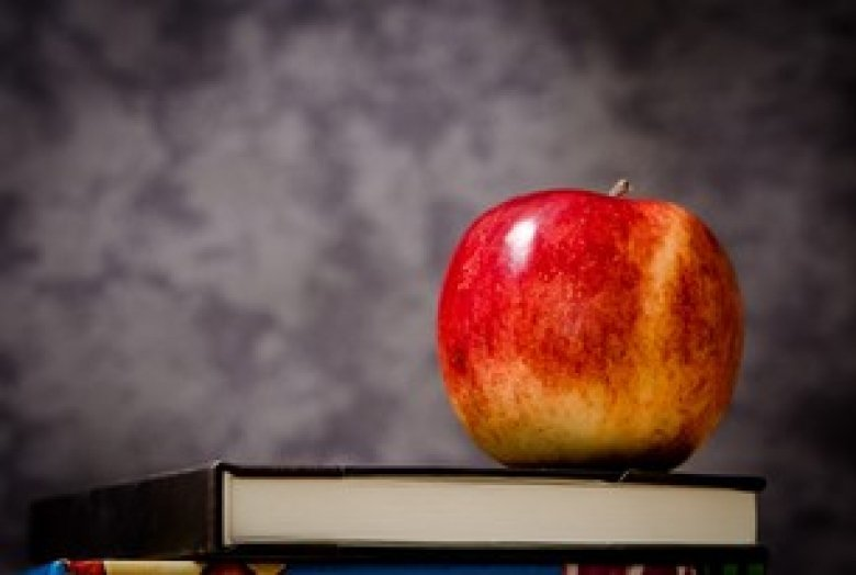 A red apple on top of a book